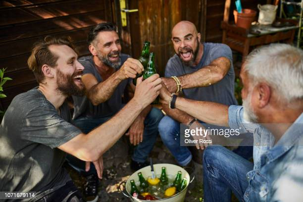 cheerful friends sitting at garden shed clinking beer bottles - only men stock-fotos und bilder