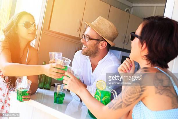 Joyeux amis assis sur pavillon et boire un cocktail-soleil