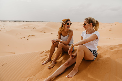 Cheerful Friends Sitting On Sand At Desert Against Sky - gettyimageskorea