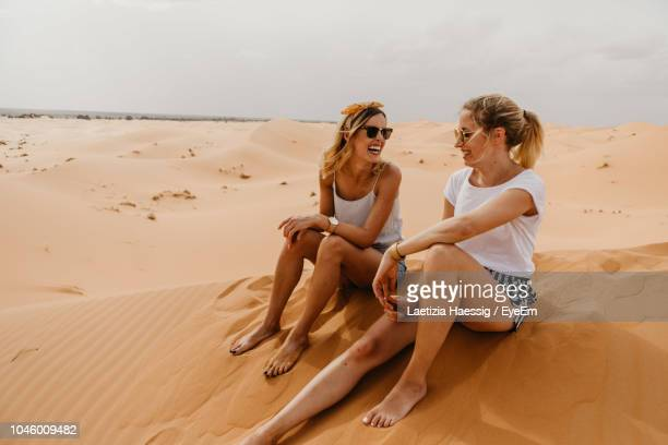 cheerful friends sitting on sand at desert against sky - femme marocaine photos et images de collection