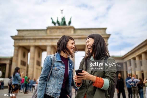 cheerful friends standing against brandenburg gate - 25 29 anos imagens e fotografias de stock