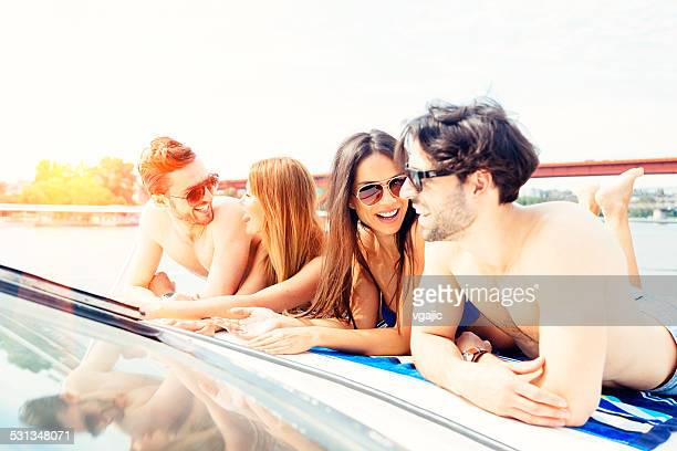 Cheerful Friends Sunbathing on Yacht Together.