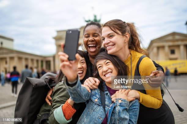 cheerful friends taking selfie against brandenburg gate - cultures stock pictures, royalty-free photos & images