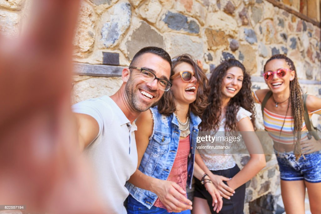 Cheerful friends taking selfie on street : Stock Photo