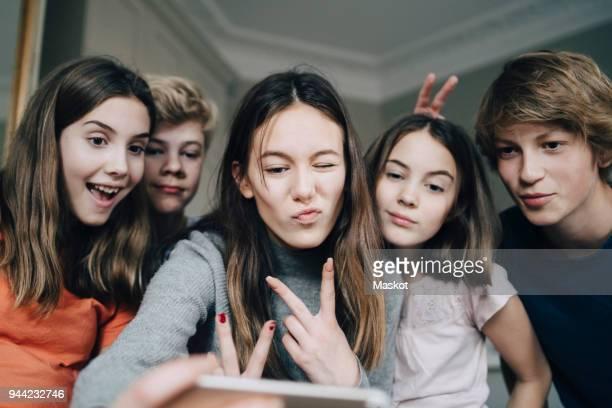 cheerful friends taking selfie through mobile phone at home - kind vor der pubertät stock-fotos und bilder