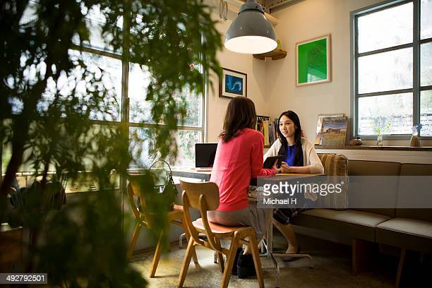 cheerful friends talking  at  cafe