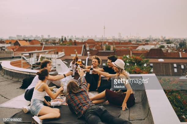 cheerful friends toasting beer while relaxing on terrace at city - celebratory toast stock pictures, royalty-free photos & images