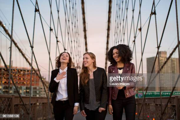 cheerful friends walking on brooklyn bridge against clear sky - tres personas fotografías e imágenes de stock