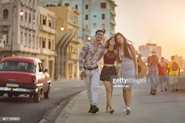 Fröhliche Freunde gehen auf Bürgersteig während des Sonnenuntergangs