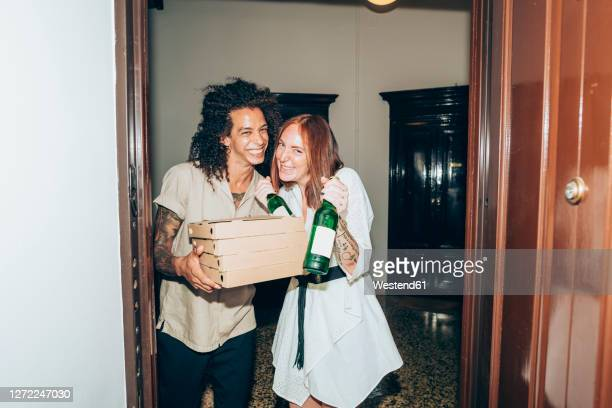 cheerful friends with beer bottle and pizza boxes at entrance of home during party - black and white photos et images de collection