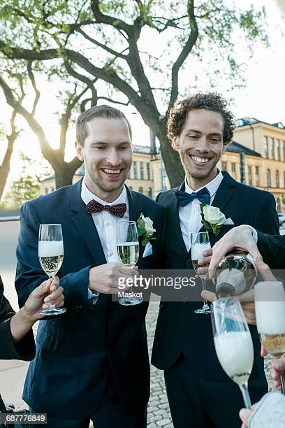 Cheerful friends with champagne during wedding ceremony