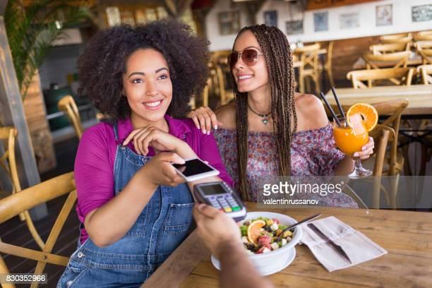 Vrolijke frineds met behulp van slimme telefoon voor mobiel betalen
