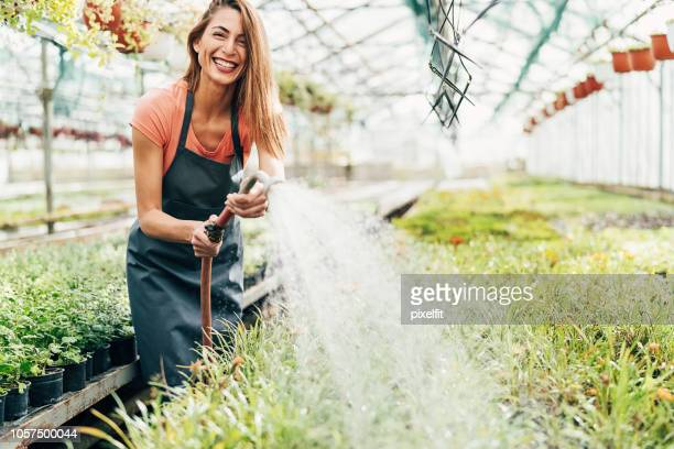 Cheerful gardener watering plants in the greenhouse
