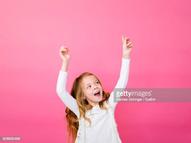 cheerful girl against pink background - arms raised stock pictures, royalty-free photos & images