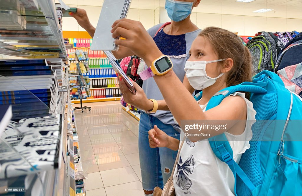 Cheerful Girl Buying Workbooks on Back To School Shopping with her Mother Wearing Protective Face Mask - stock photo : Stock Photo