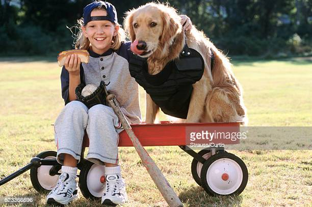 Cheerful Girl Dressing Her Dog Up as a Baseball Catcher