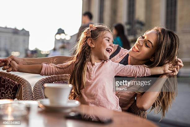 Cheerful girl having fun with her young mother at cafe.