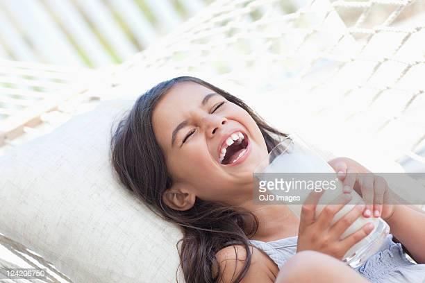 Joyeuse fille rire dans un hamac en tenant un
