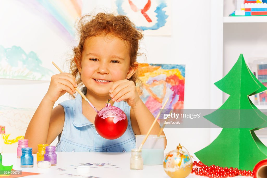 Cheerful girl painting New Year while sitting