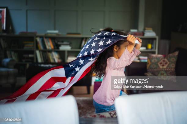 cheerful girl running with american flag at home - stars and stripes stock pictures, royalty-free photos & images