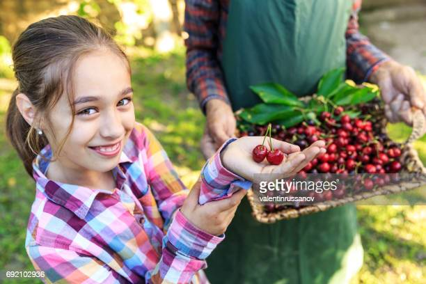 Cheerful girl showing cherry fruits