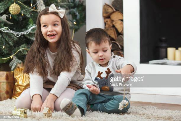 Cheerful girl sitting by brother on rug at home