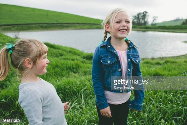 Cheerful girl standing with sister on grassy field by lake