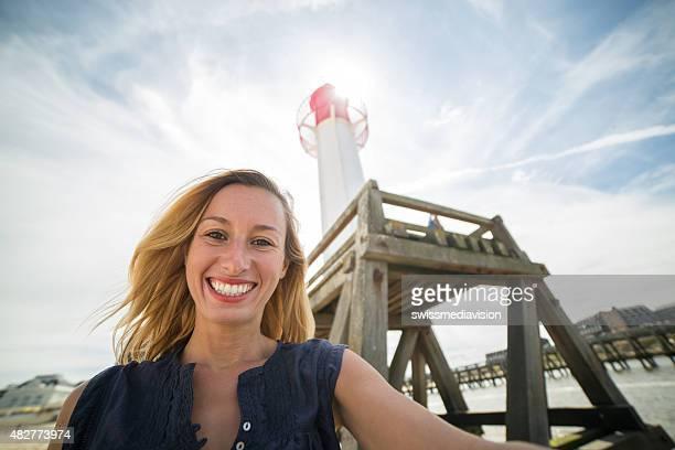Joyeuse fille prenant selfie dans la salle Normandy-France près de lighthouse