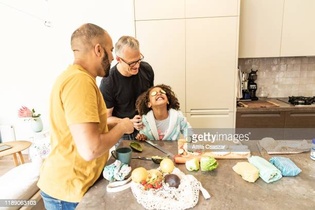 Cheerful girl with dads playing with cucumber on her eyes