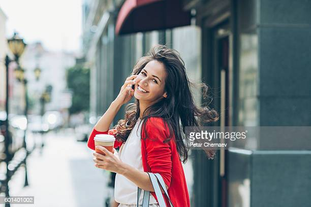 Cheerful girl with phone on the street looking back