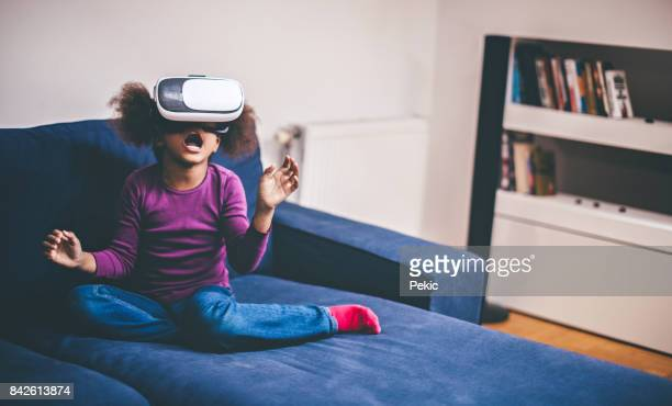 Cheerful girl with virtual reality goggles