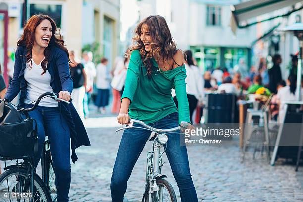 Cheerful girlfriends riding bikes
