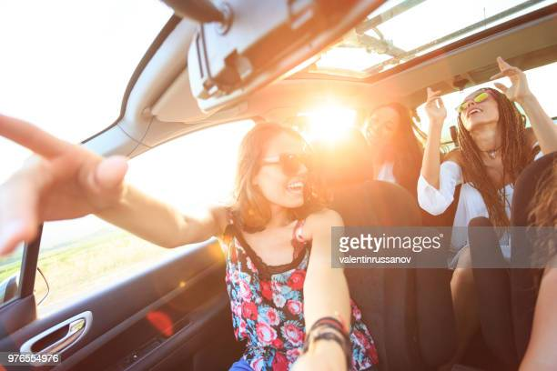 cheerful girlfriends traveling with a car - cantare foto e immagini stock