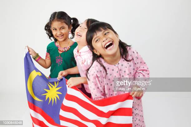 cheerful girls holding malaysian flag while standing against white background - malaysian culture stock pictures, royalty-free photos & images