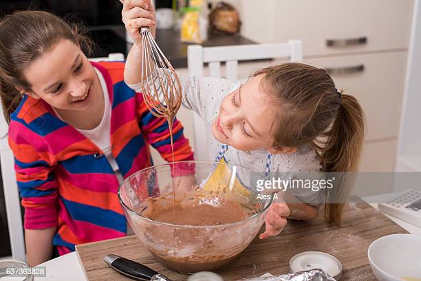 Cheerful girls making muffins
