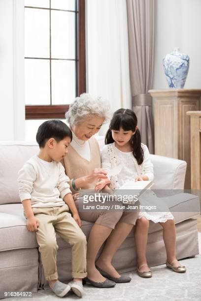 cheerful grandmother and grandchildren looking at photo album - asian granny pics stock photos and pictures