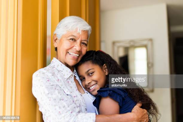 Cheerful grandmother embracing teen granddaughter