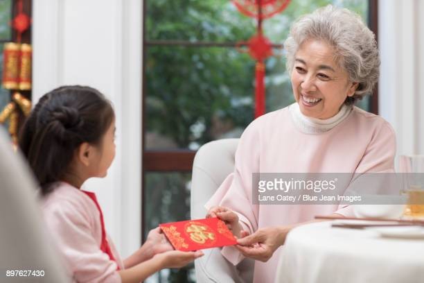 Cheerful grandmother giving red pocket to granddaughter