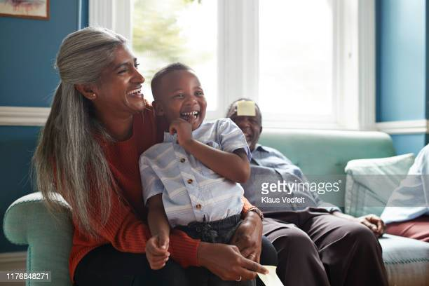 Cheerful grandmother with grandson sitting on sofa