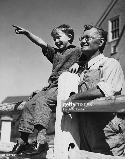 cheerful grandson pointing and grandfather looking towards - {{ contactusnotification.cta }} stockfoto's en -beelden