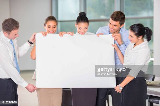Cheerful group of business people holding a placard