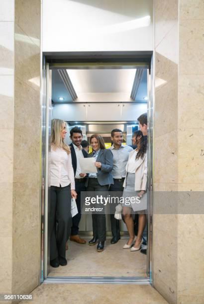 alegre grupo de empresários no elevador indo até seu escritório - elevador - fotografias e filmes do acervo