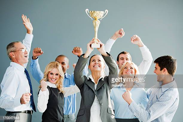 cheerful group of businesspeople winning the cup. - award stock pictures, royalty-free photos & images