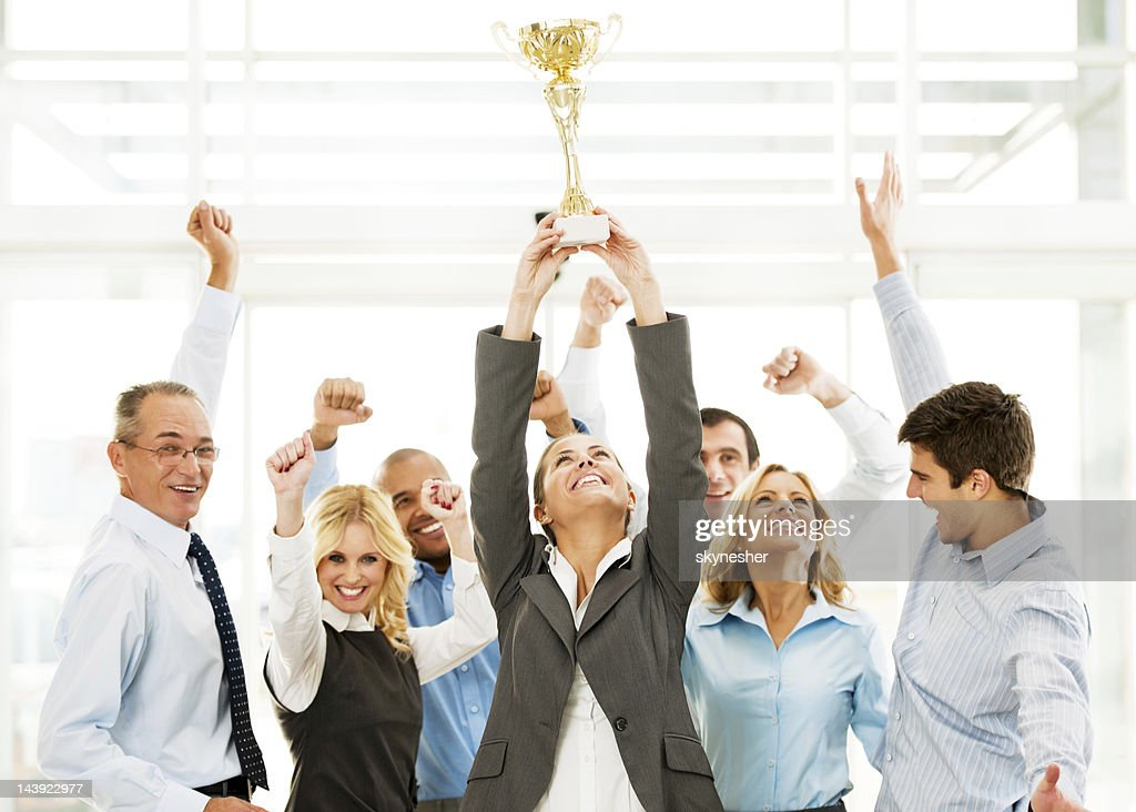 Cheerful group of businesspeople winning the cup with hands up. : Stock Photo