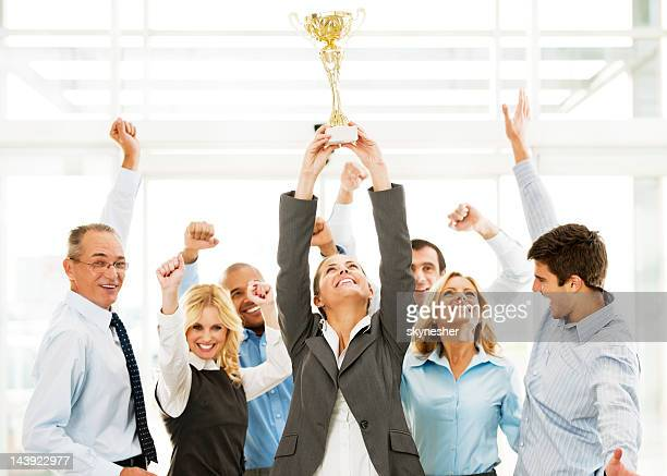 cheerful group of businesspeople winning the cup with hands up. - award stock pictures, royalty-free photos & images