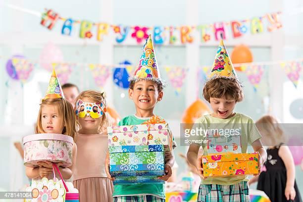 Joyeux groupe d'enfants tenant anniversaire présente.