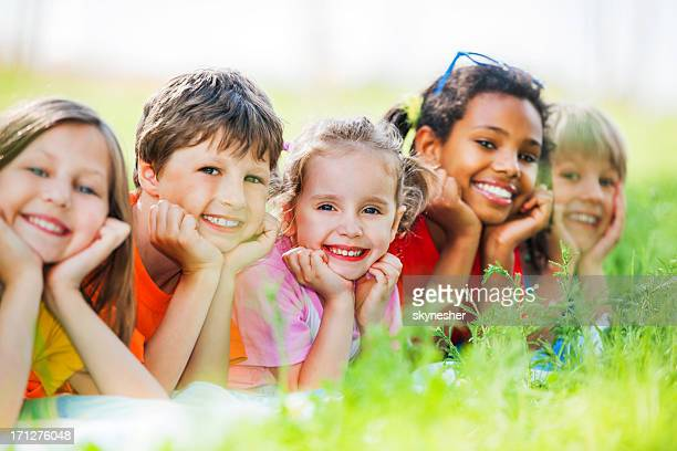 Cheerful group of children lying in the park.