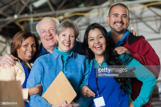 cheerful group of food bank volunteers - non profit organization stock pictures, royalty-free photos & images