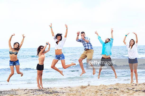 Cheerful group of friends celebrating on beach