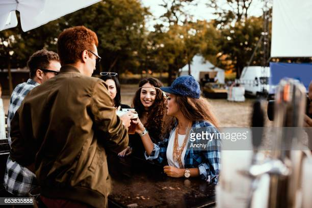 Cheerful group of friends drinking beer on the campsite at a music festival